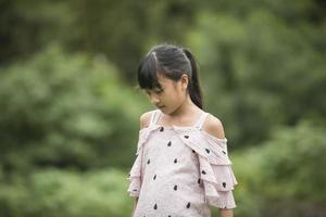 Portrait d'une petite fille asiatique marchant dans le parc photo