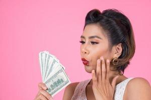 heureuse belle femme tenant des dollars