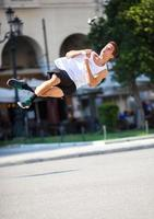 Jeune homme effectuant un saut périlleux dans la rue photo