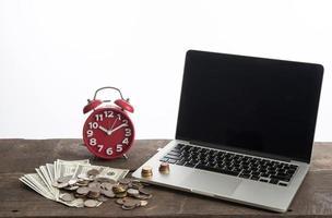 Ordinateur portable avec pièces de monnaie et banque en dollars isolé sur fond blanc photo