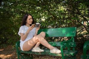 Portrait d'une femme décontractée heureuse assis sur un banc avec café et téléphone dans le parc photo
