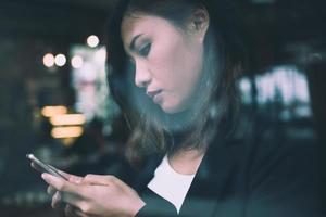 Young woman reading news sur téléphone mobile pendant le repos dans un café photo