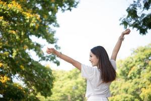 Portrait d'une adolescente levant les bras et riant dans le parc