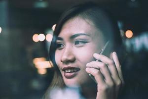 Jeune femme parlant au téléphone mobile pendant le repos dans un café photo