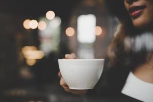 Jeune femme se détendre en buvant du café au café photo