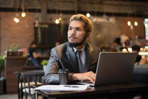jeune homme d'affaires tenant une tasse de café tout en travaillant sur un ordinateur portable dans un café photo