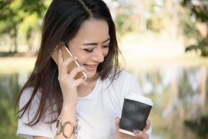 Belle jeune femme tenant une tasse de café jetable tout en parlant au téléphone photo