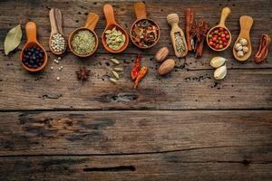Épices dans des cuillères en bois sur un fond en bois avec espace copie photo
