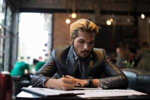 Bel homme d'affaires écrit sur ordinateur portable avec une tasse de café au restaurant photo