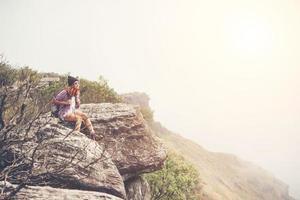 jeune randonneur avec sac à dos est assis sur le bord de la falaise