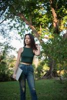 Belle jeune femme tenant un ordinateur portable tout en allant se détendre dans un parc photo