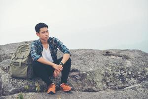 jeune randonneur hipster avec sac à dos assis au sommet de la montagne photo