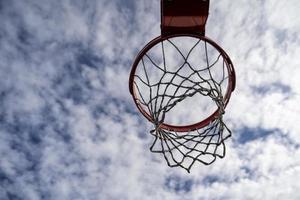 jante de basket-ball en plein air sur une journée nuageuse et ensoleillée photo