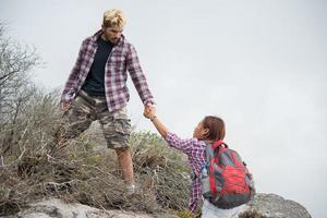 jeune homme hipster aidant femme escalade montagne photo