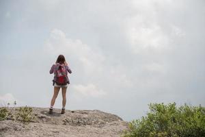 Randonneur avec sac à dos debout au sommet d'une montagne et profiter de la vue sur la nature