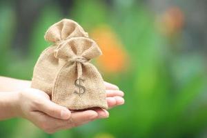 mains tenant deux sacs de jute avec symbole dollar photo
