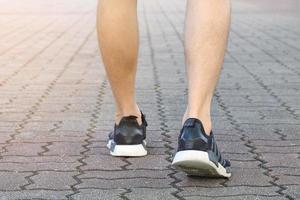 Les jambes de l'homme avec des chaussures de tennis sur la surface de la brique photo