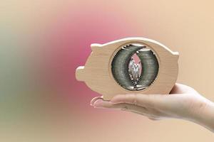 main tenant tirelire avec des piles de pièces à l'intérieur photo