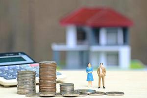 Des piles de pièces à côté de la calculatrice et des poupées miniatures homme et femme avec maison miniature en arrière-plan photo