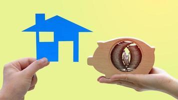 Mains tenant une maison modèle et tirelire en bois avec des piles de pièces à l'intérieur sur fond jaune photo
