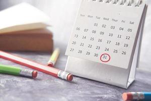 Concept de date limite avec marque rouge sur la date du calendrier avec livre et crayons sur table photo
