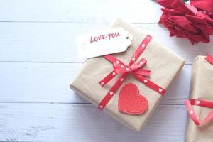 Vue de dessus du coffret cadeau, enveloppe et fleur rose sur fond blanc photo