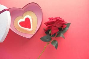 Vue de dessus du gâteau en forme de coeur, boîte-cadeau et fleur rose sur fond rouge photo