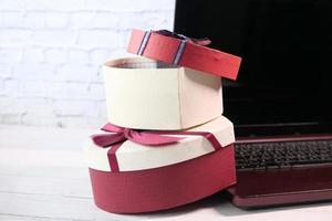 pile de coffrets cadeaux et ordinateur portable sur table photo