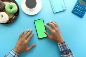 Vue de dessus de la main de l'homme à l'aide de smartphone avec des beignets et du thé sur fond bleu