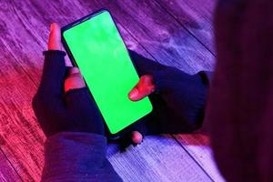 La main d'un pirate informatique volant des données d'un smartphone dans une lumière sombre au néon photo