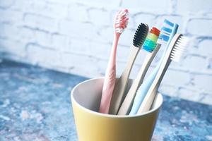 Brosses à dents colorées dans une tasse blanche contre un mur photo