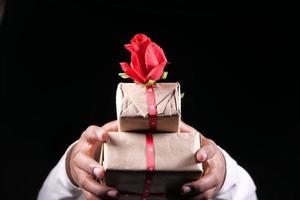 Main de l'homme non reconnu tenant une boîte-cadeau isolée sur fond noir photo