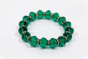 bracelet avec des gemmes vertes isolé sur fond blanc photo