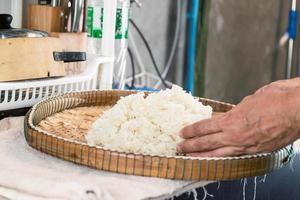 Mains plaçant du riz blanc cuit à la vapeur sur un plateau en bambou photo