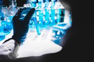 Main dans un gant bleu tenant un flacon de liquide bleu avec des flacons de liquide bleu en arrière-plan photo