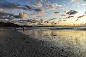 silhouette de personnes au coucher du soleil bleu et jaune à la plage