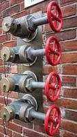 Vannes de pompe à incendie rouge sur un mur de briques photo