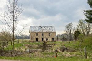 Vieille maison en pierre sur une colline verte sous un ciel nuageux