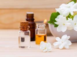 bouteilles d'huile d'arôme arrangées avec du jasmin