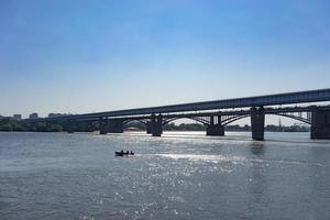 Les gens dans un bateau à côté d'un pont sur la rivière ob à Novossibirsk, Russie photo