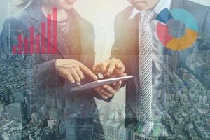 double exposition de deux hommes d'affaires à l'aide d'une tablette photo