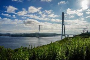 Paysage marin de champ vert par Golden Horn Bay et le pont zolotoy avec ciel bleu nuageux à Vladivostok, Russie photo