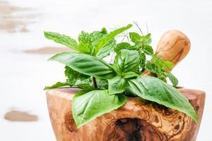 herbes vertes dans un mortier en bois photo