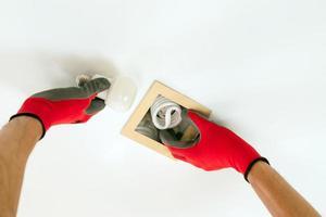 deux mains dans des gants remplaçant une ampoule fluorescente par une ampoule led photo