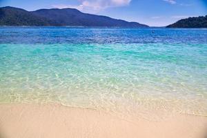 vagues, eau bleue et montagnes avec un ciel bleu nuageux sur une plage de l'île de Koh Lipe en Thaïlande photo