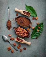 poudre de cacao et fèves de cacao sur un fond de béton foncé photo