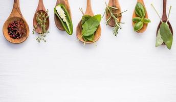 épices et herbes en cuillères sur blanc photo