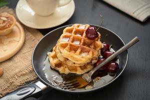 Gaufres et cerises au miel dans une casserole, tartelettes croustillantes aux amandes et une tasse de café sur table noire photo