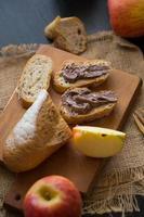 Pommes entières et tranchées avec baguette en tranches avec un beurre au chocolat sur planche de bois sur une table en bois foncé photo