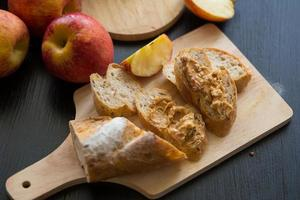 Pommes entières et tranchées avec baguette en tranches sur planche de bois sur une table en bois sombre photo